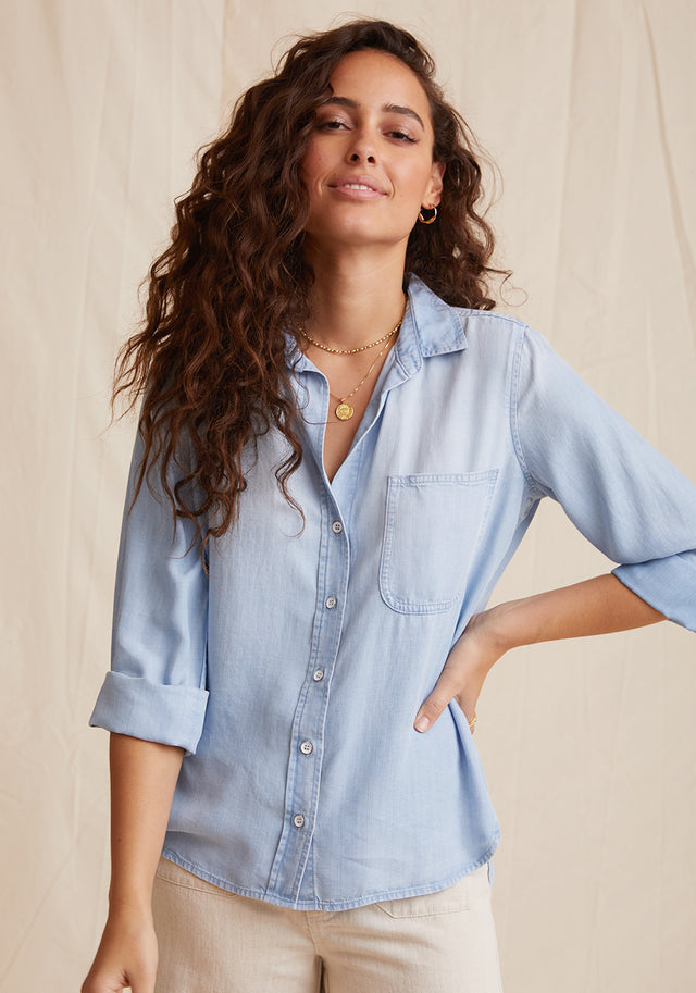 Front View: Womens Light Denim Wash Long Sleeve Button Down Shirt With Front Pocket and Collared Neckline