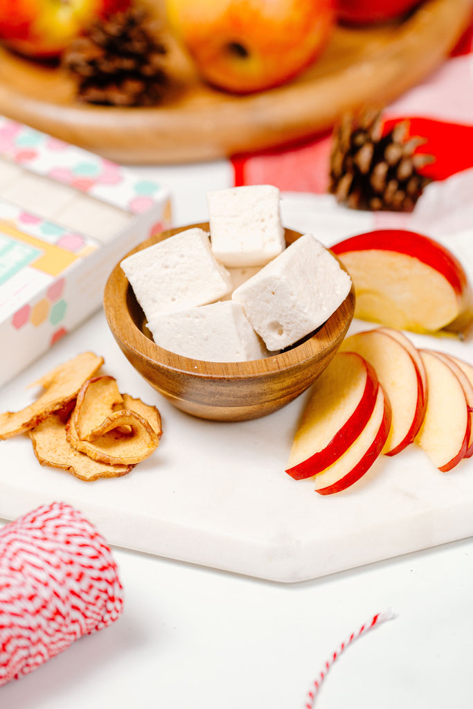 Apple Cinnamon marshmallows in a bowl next to apple slices and cinnamon sticks