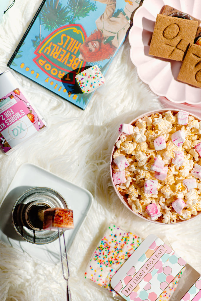 XO marshmallow shows off all their favorite indoor glamping snacks such as popcorn with marshmallows and s'mores