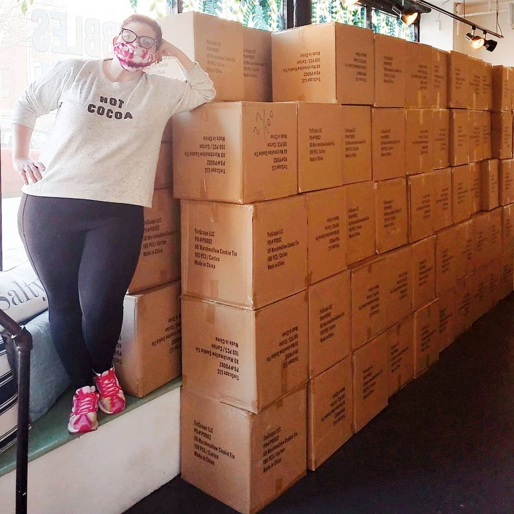 Kat Connor, co founder of XO Marshmallow, stands in front of 10,000 hot cocoa tins