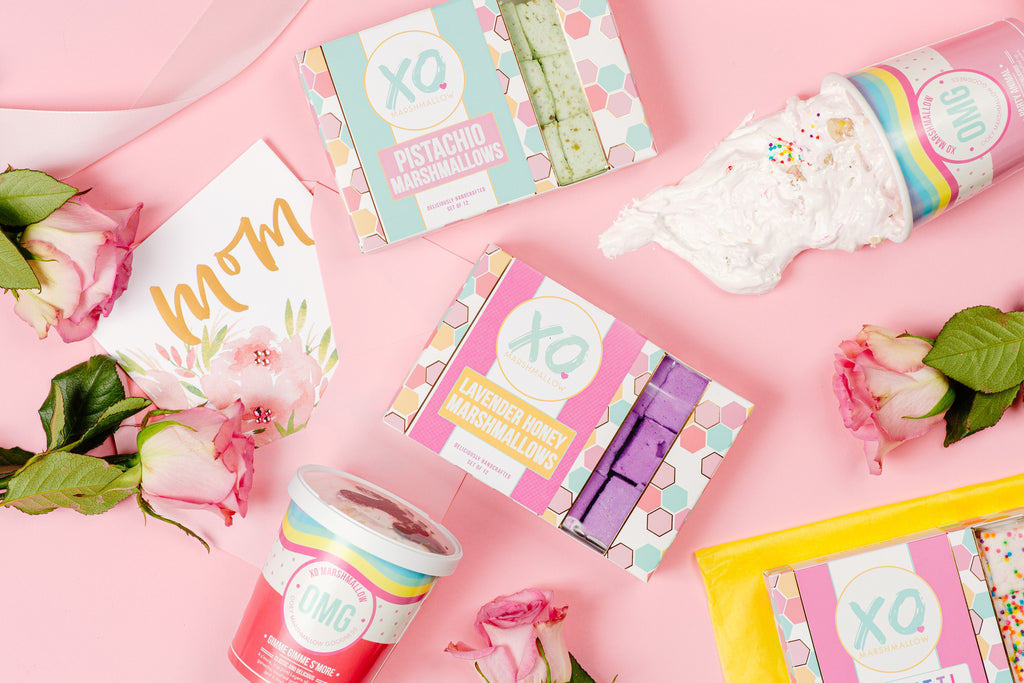 A group of all of our XO Marshmallow mother's day favorites with a card, flowers and a ribbon