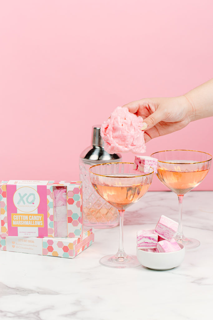 A hand adding cotton candy to the top of champagne and adding a garnish of cotton candy marshmallows