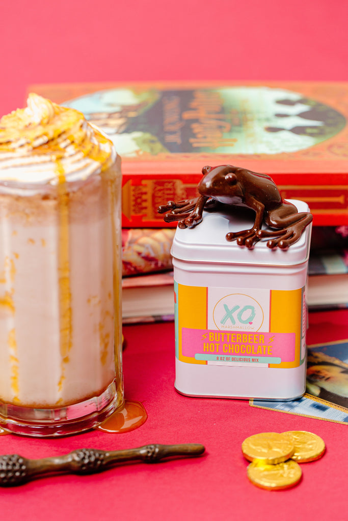 A chocolate frog on top of a tin of our butterbeer cocoa mix