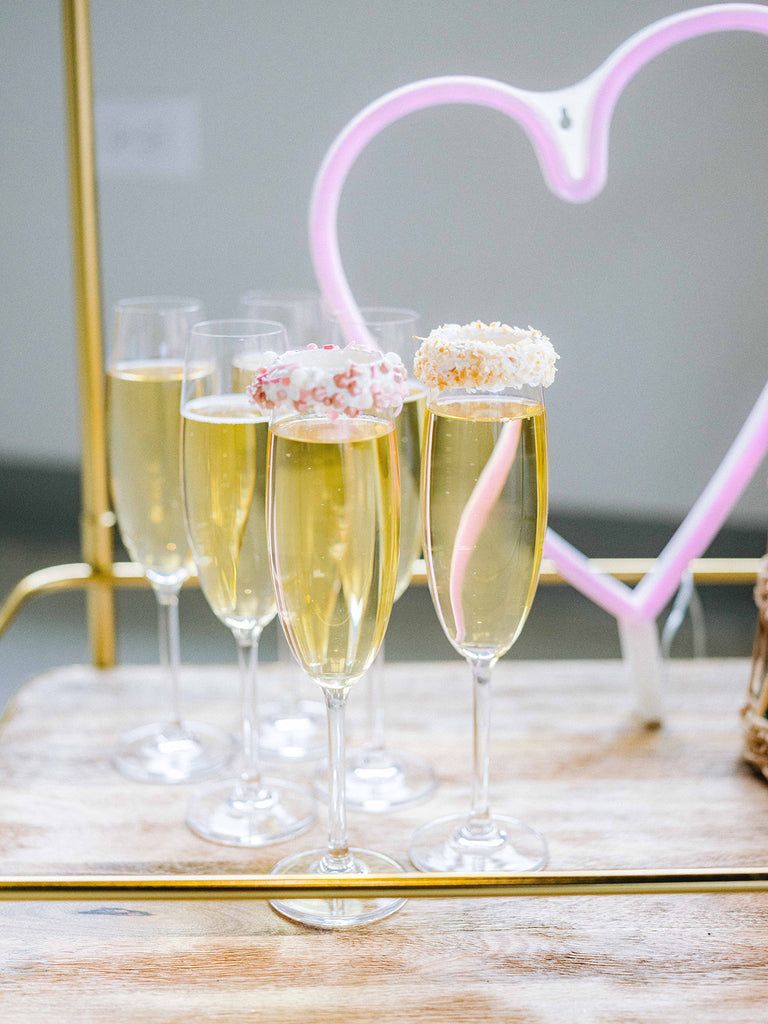 A glass of champagne whose rim has been dipped in vanilla xo marshmallow ooey marshmallow goodness and rolled in sprinkles
