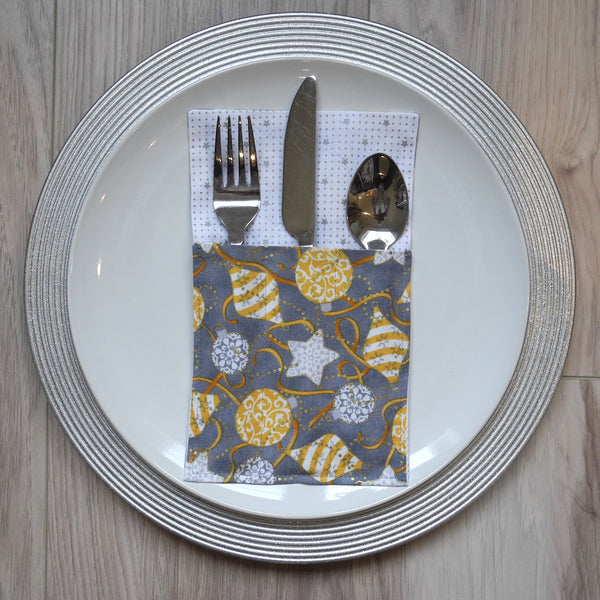 Cutlery holder in silver and gold Christmas ornament fabric on a silver charger