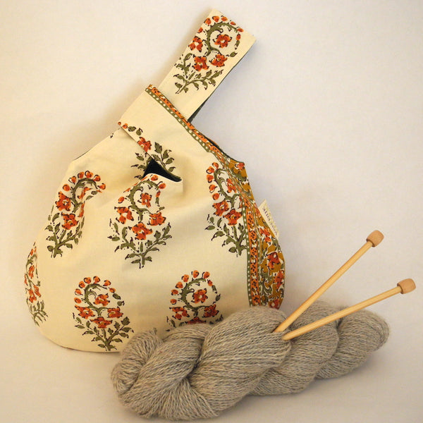 knot bag shown with yarn and needles