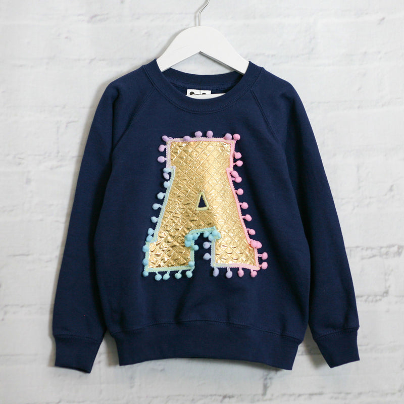 LETTER SWEATER IN GOLD WITH PASTEL POM POM TRIM