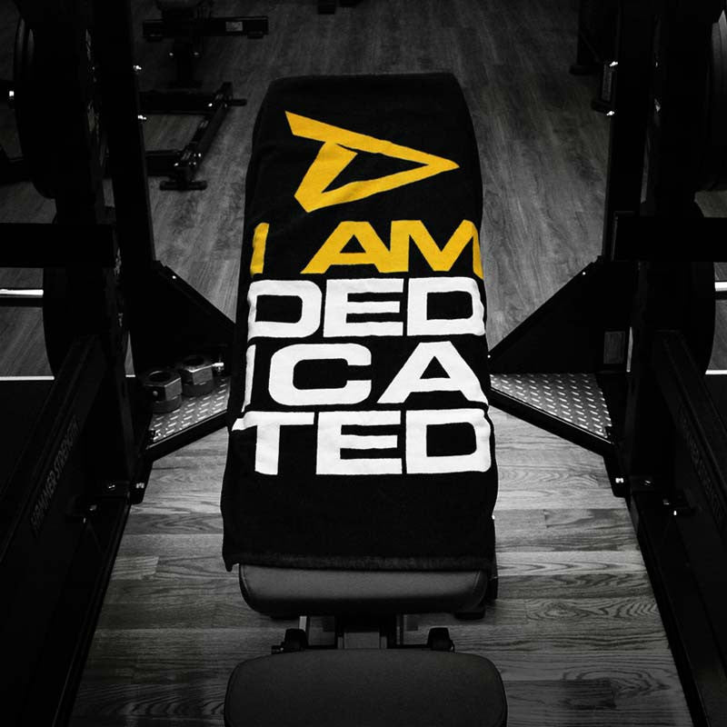 Towel with I Am Dedicated logo on bench