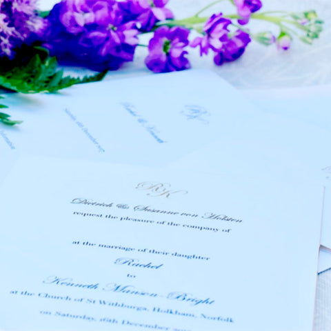 The gold engraved monograms of the Holkham wedding Invitations with black raised printed text.
