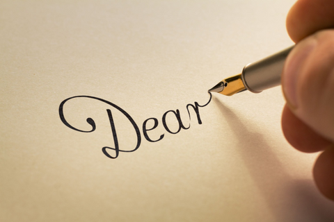 A fountain pen being used to write 'Dear' at the top of a headed sheet