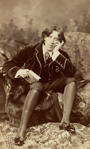 Oscar Wilde is seated leaning on an elbow with a book in hand