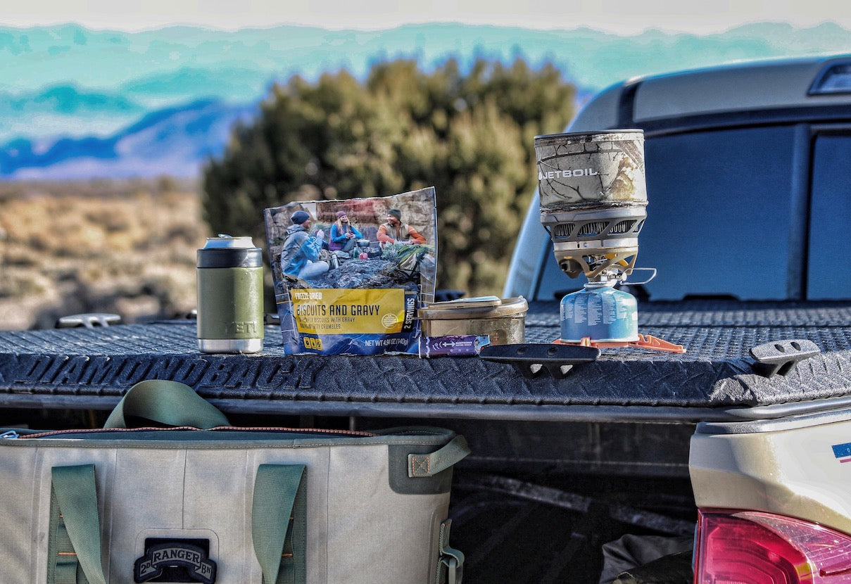 Jetboil portable cooking stove, Mountainhome freeze-dried biscuits & gravy, a Yeti Rambler Colster, and a Ranger range bag on a DiamondBack HD truck bed cover on a Toyota Tacoma