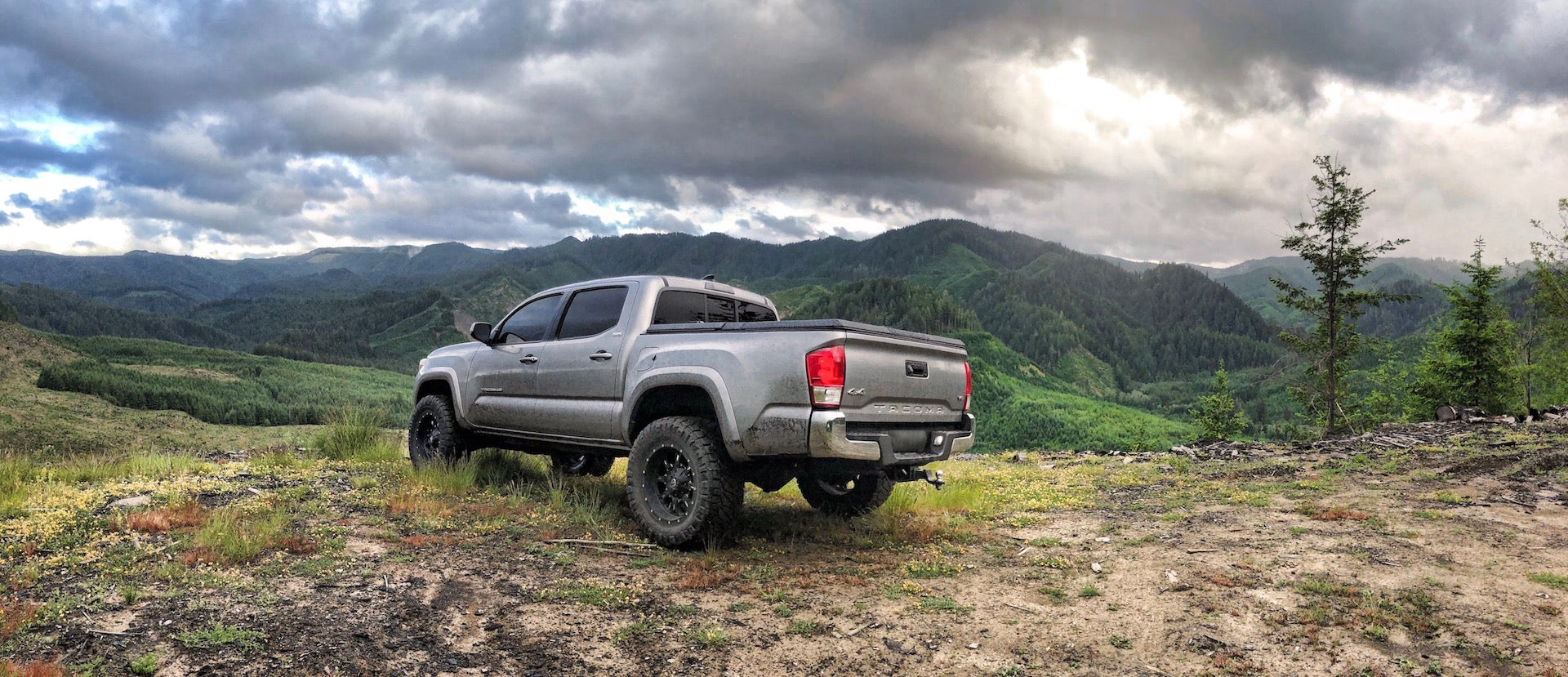 A Toyota Tacoma with a Diamondback SE truck bed cover on it looks over green mountains