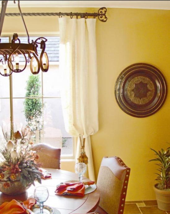 bright yellow walls in a country style dining room with intricate curtain rod and finial detail