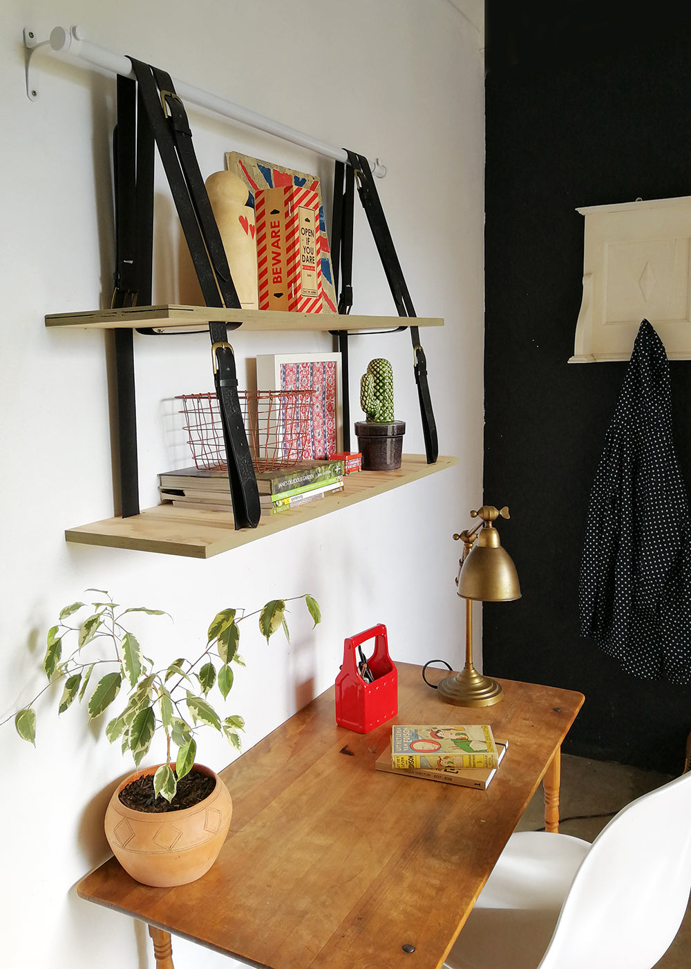 hanging shelf in home office with small wooden desk and pot plant