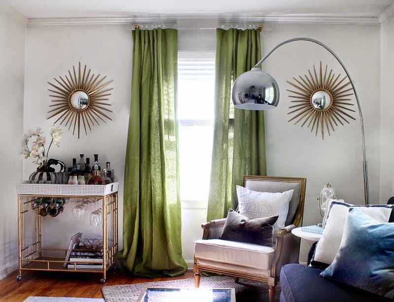 eclectic room with gold sun mirrors green curtains and acrylic curtain rod