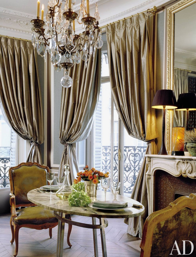 flamboyant french dining area with gold curtains and chandelier
