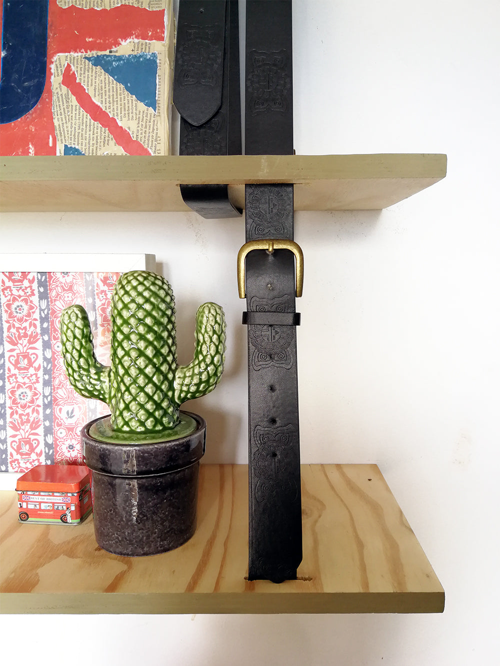 close up of hanging shelf in home office with glass cactus and belt detail