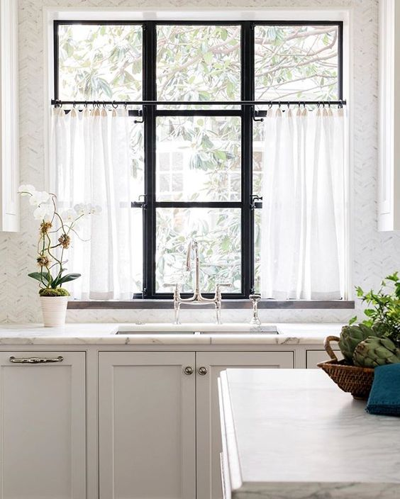 kitchen with marble counter top and spring cafe curtains