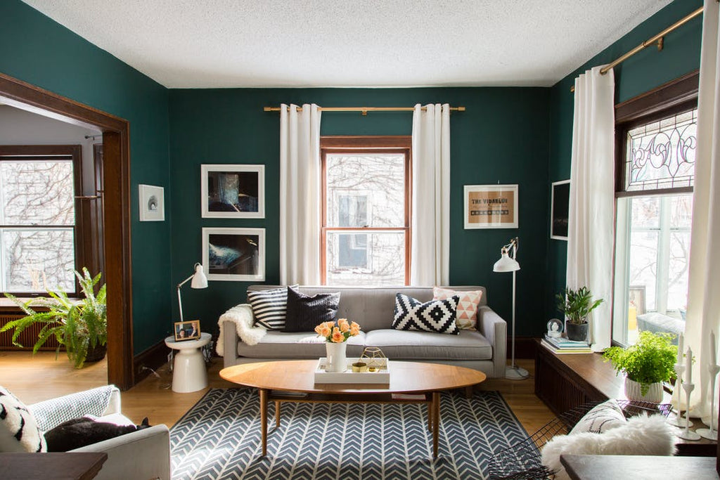 living room with green walls and golden curtain rods