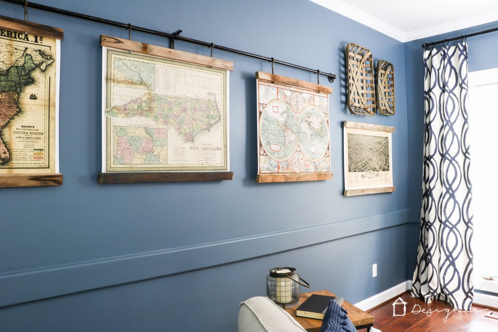 printed maps hanging from a curtain rod against a blue wall