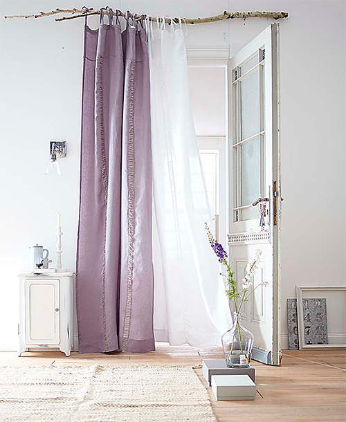 rustic minimalist pink and white curtains suspended by a natural wood branch as curtain rod