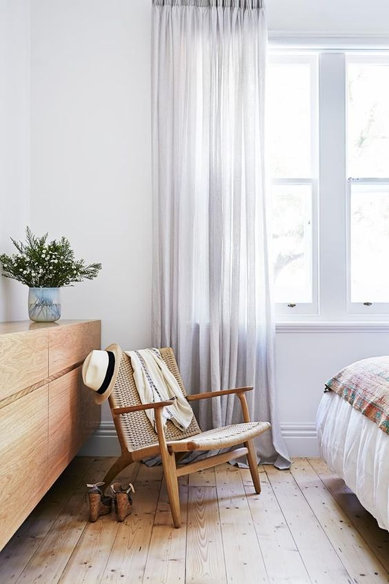 summery bedroom with woven chair wooden floors and grey curtains