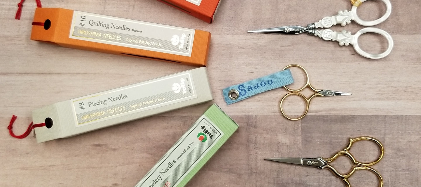 A selection of embroidery floss and ornate embroidery scissors imported from Sajou of Paris.