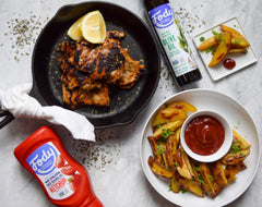 bottle of fody ketchup, potato wedges, fody garlic-infused olive oil, and grilled chicken in a cast iron pan