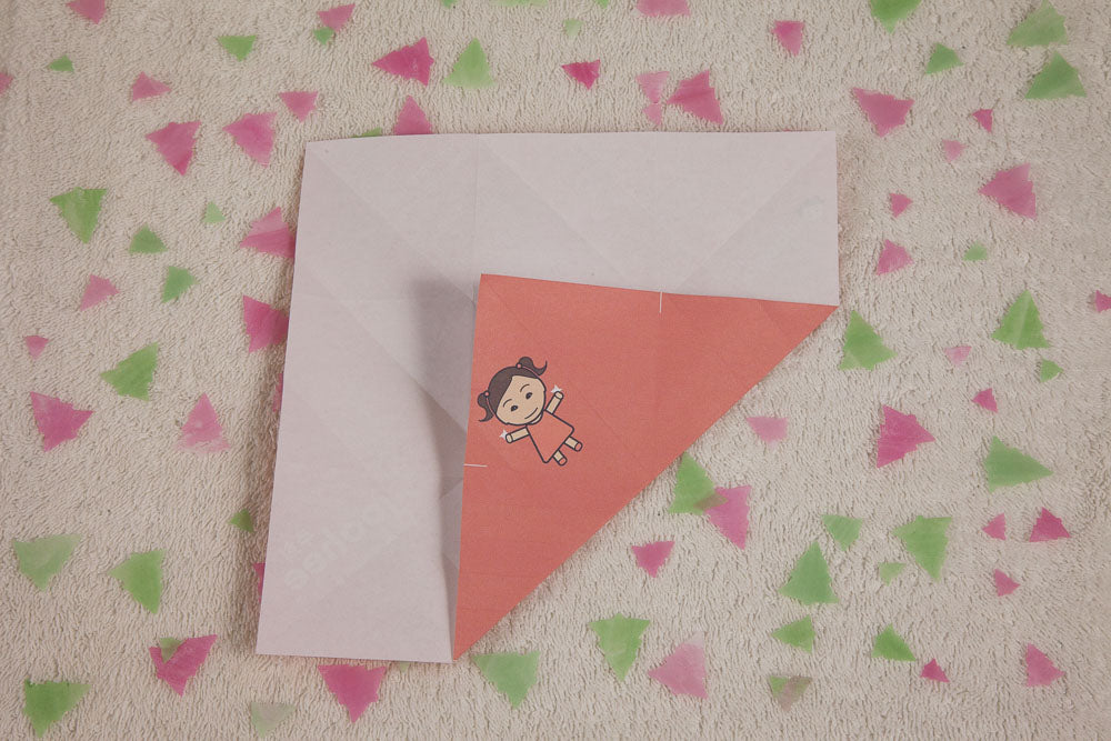 Step 5: Fold each corner into and across to the intersection of the opposite thirds folds, then lay the paper open.