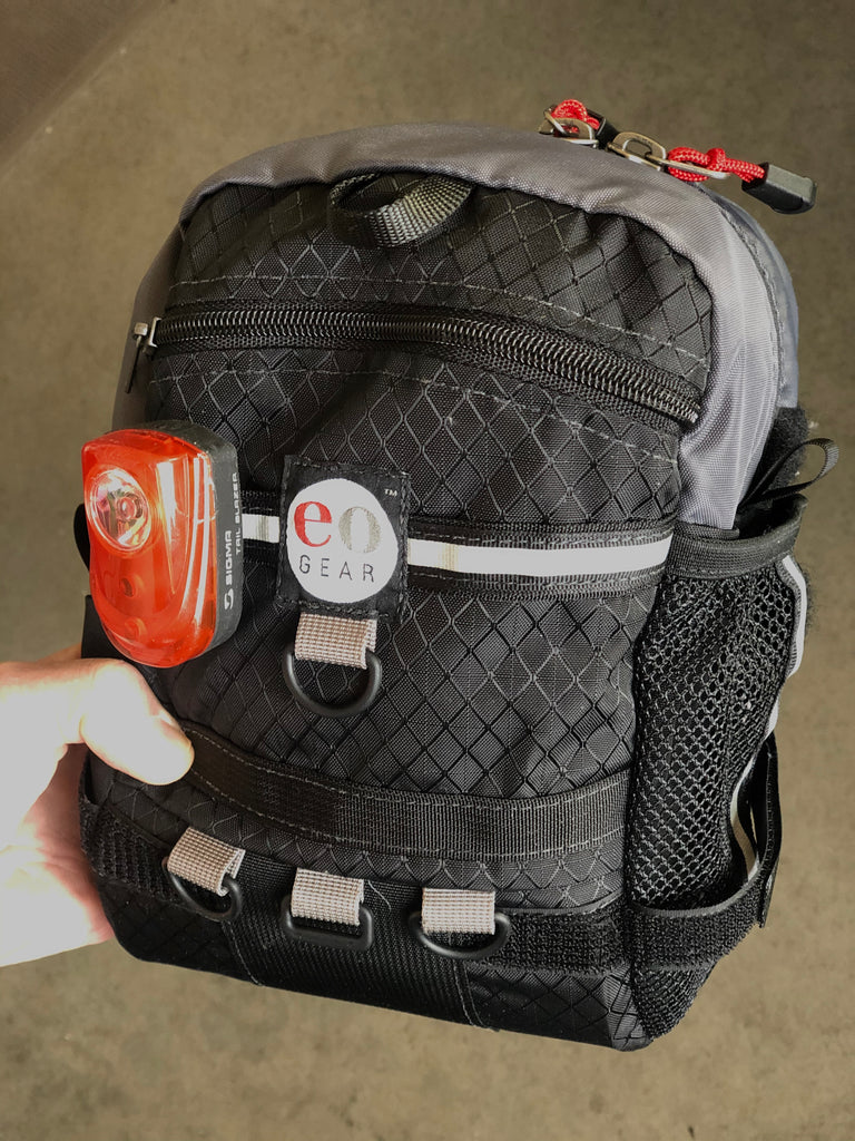 There is a hidden slot for a blinky tail light (to the left of the label), however, this bag tilts downward rendering if less effective. We recommend mounting lights on your seat stay instead.