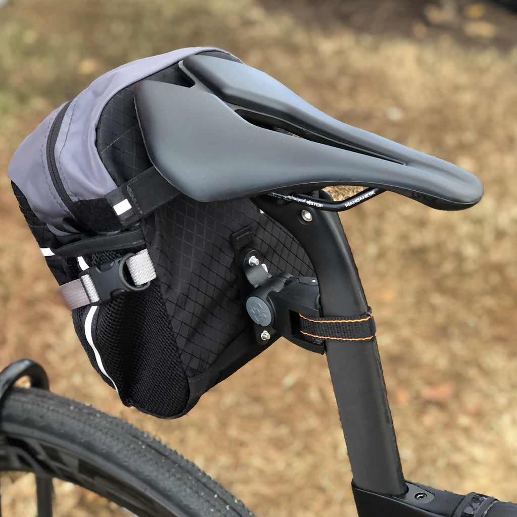 The bag will attach to oval seatposts like this style because the back edge of the post is nearly round (pix is an old style 4.8 bag, which uses the same hardware as the current 2.3 bag). Shown on a Pinarello gravel bike).
