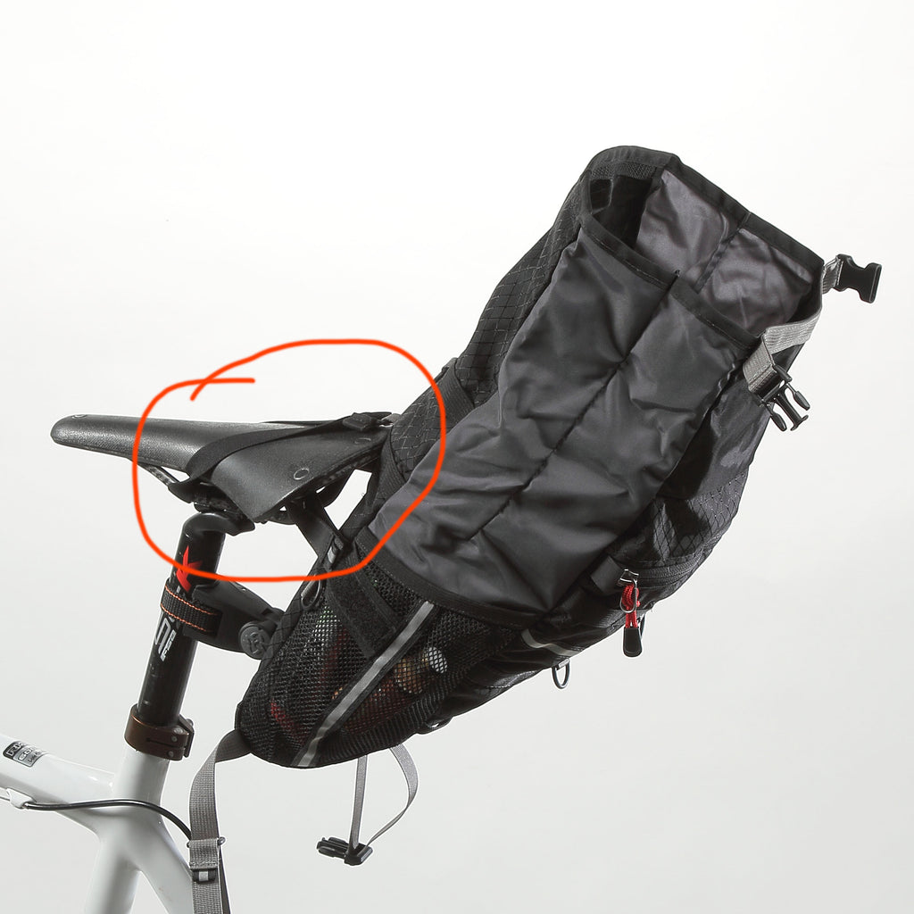 Included is an elastic strap which you can slip over the saddle while packing, yielding a more upright position of the bag.