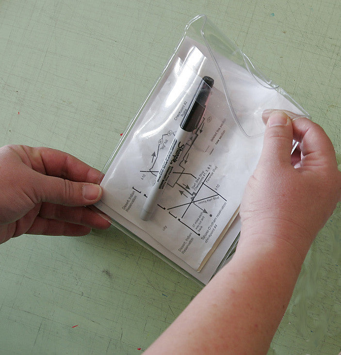#4. Insert your cue sheets face down into the pouch, then tuck the flap under the band as shown.