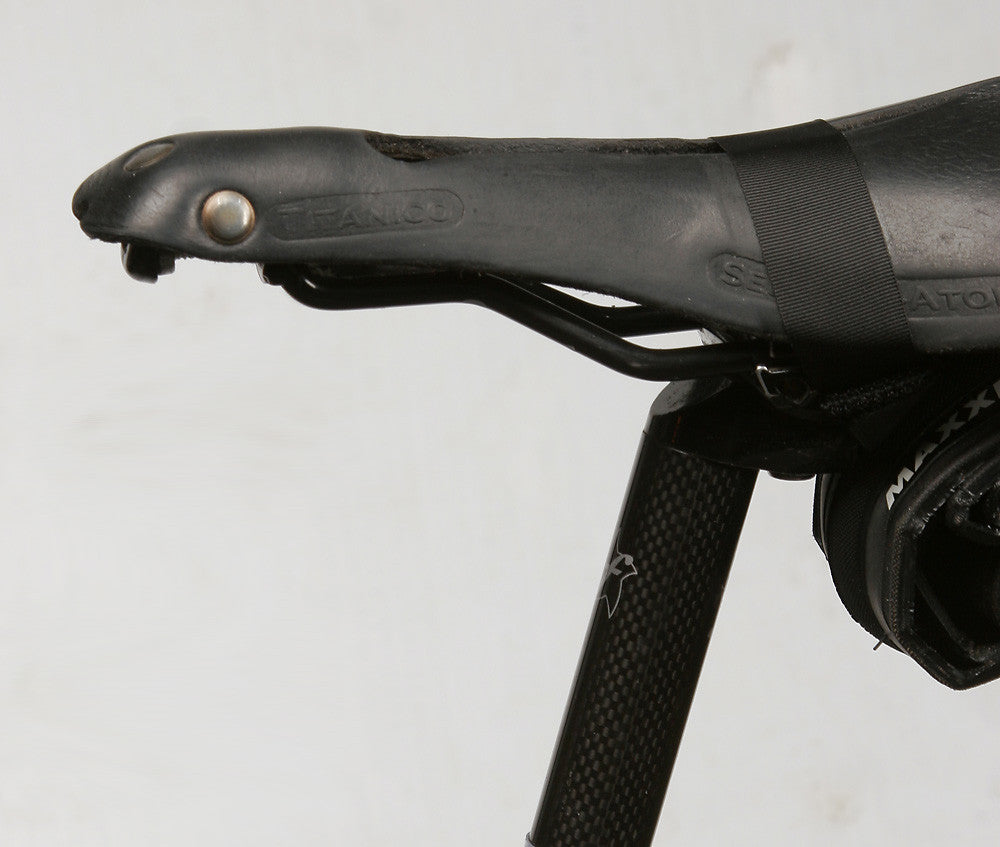 "The ""over the top"" strap squeezes the sides of the leather, making its shape more like a conventional shaped saddle."