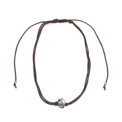 Cotton necklace with alluring silver metallic stone pendant. Rich, dark brown cotton cords with silver brass bead tie closure adjust smoothly to length of choice.