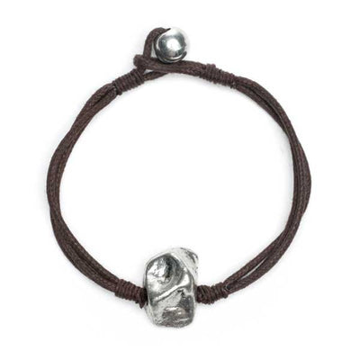 Cotton bracelet with alluring silver metallic stone pendant. Rich, dark brown cotton cords with silver brass bead tie closure adjust smoothly to length of choice.