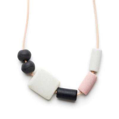 Closeup of Neutral Kalahari Necklace on a leather cord with black, pink and white glass beads.