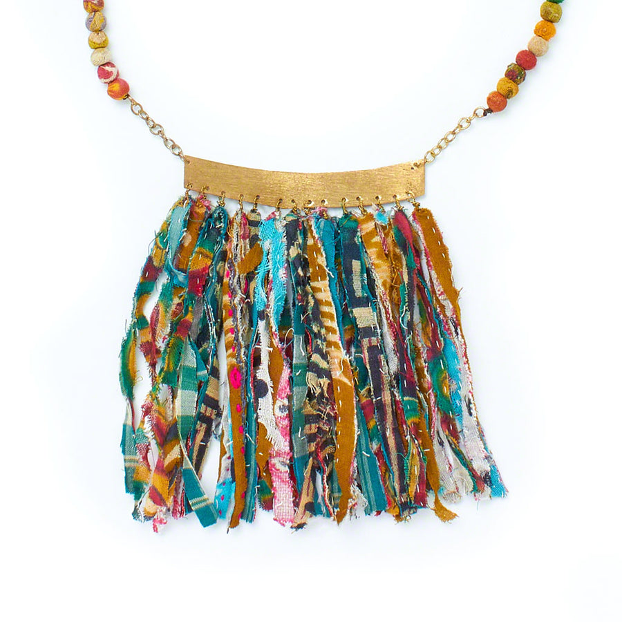 A lightweight, unique statement necklace like no other. A fringe of repurposed Kantha fabric strips hangs from a brushed gold band.