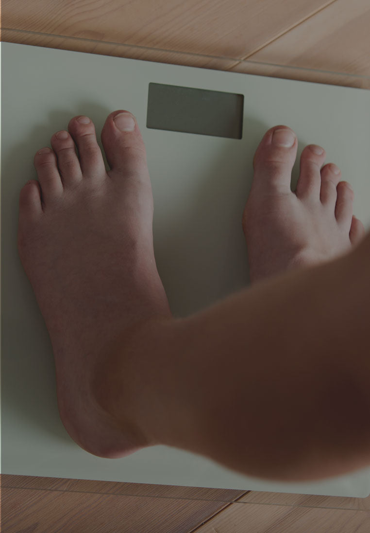 A person standing on a scale measuring their weight