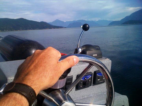 Image of a man's hand on the steering wheel of  boat with ocean and mountains ahead