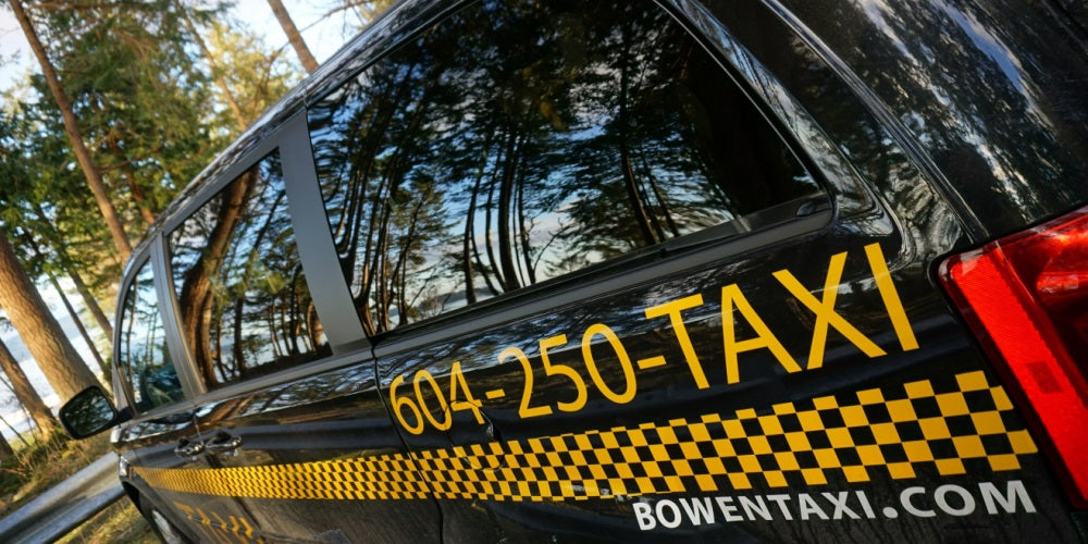 Side image of Bowen Land taxi parked in front of a wooded park.