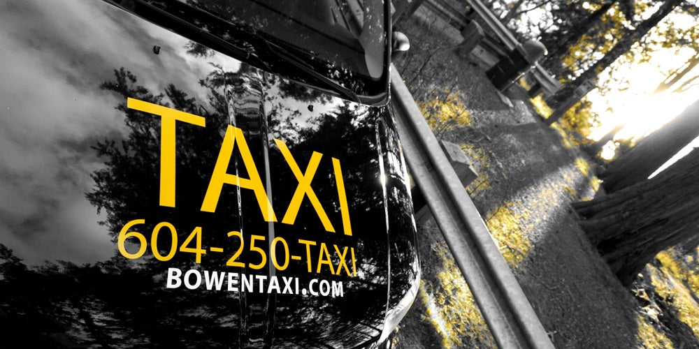 Front hood of the Bowen land taxi displays the phone number and website is seen parked near a grove of sunny trees.