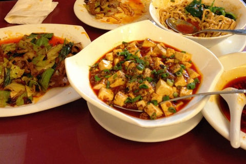 Image of Chinese food in plates on a table that was delivered by Bowen Food Delivery