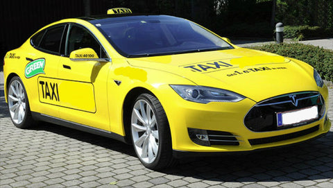 Yellow Tesla Taxi cab parked on a cobble stone driveway