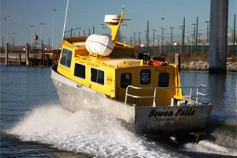 A yellow and silver boat, the Bowen Belle is sailing towards a city