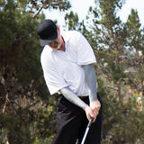 mark hits the ball on the 15th hole with grey arm sleeves on
