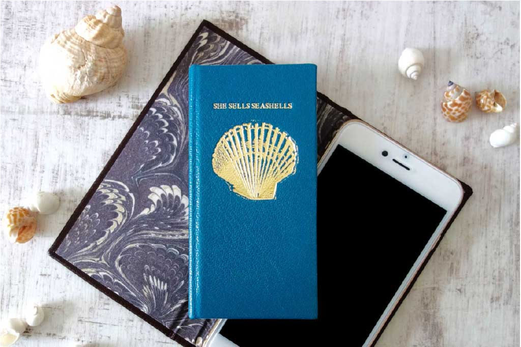 Bookshell Bindery Guide to Personalised Gifts with a personalised leather phone case with she sells seashells embossed in gold foil