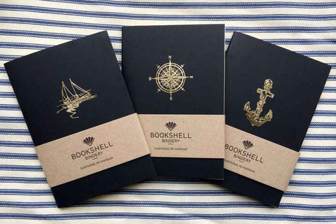 A6 pocket notebook featuring a gold foiled illustration of a boat, a compass and an anchor on the black cover