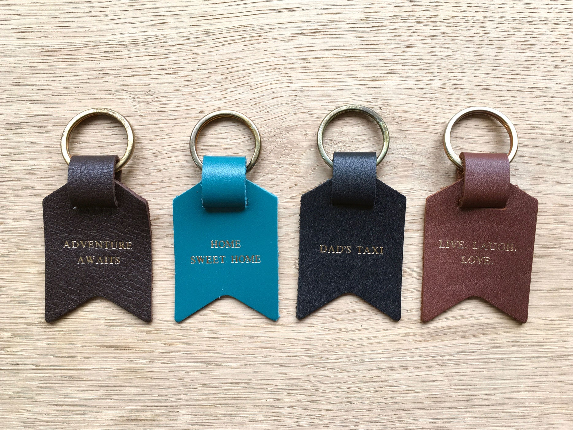 Leather keyring from Bookshell Bindery shown here in all available colours and phrases – Dark brown, blue, black, light brown